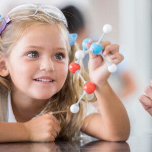Pretty Caucasian elementary schoolgirl analyzes a model of the molecular structure.